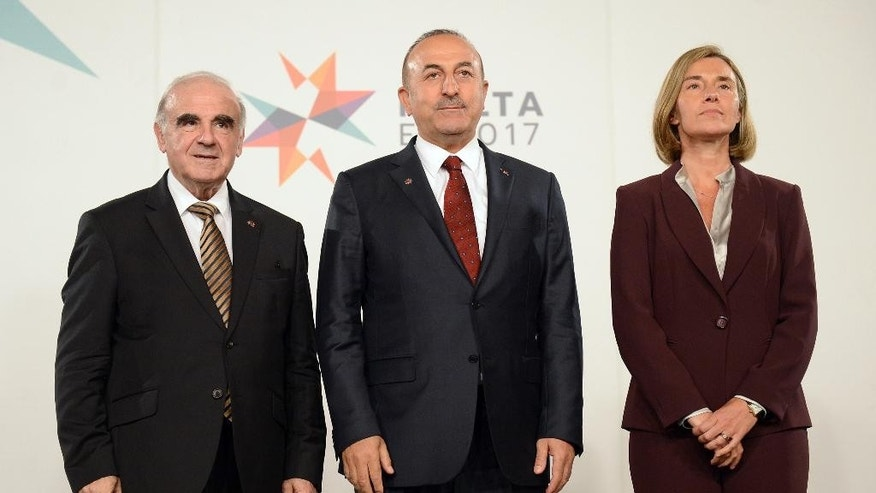 Foreign Minister of Turkey Mevlut Cavusoglu, center, stands in between Maltese Foreign Minister George Vella, left, and EU foreign policy chief Federica Mogherini, during a break of an informal meeting of the EU foreign ministers in Valletta, Malta, Friday, April 28, 2017.  (AP Photo/Rene Rossignaud)