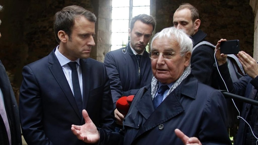 French independent centrist presidential candidate Emmanuel Macron, center, listens to Robert Hebras, right, last living survivor of the 1944 Oradour-sur-Glane massacre, during a campaign visit of the ruins in the village of Oradour-sur-Glane, central France, Friday, April 28, 2017. France's troubled wartime past is taking center stage Friday in the country's highly charged presidential race, as centrist Emmanuel Macron visited the site of France's worst Nazi massacre and Marine Le Pen's far-right party suffered a new blow over alleged Holocaust denial. (Pascal Lachenaud/Pool Photo via AP)