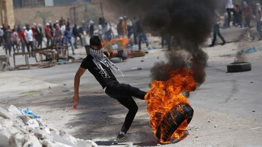 A Palestinian kicks a burning tire during clashes with Israeli forces following a rally in support of hunger-striking prisoners in Israeli jails, in the West Bank village of Beita, southeast of Nablus city, Friday, April 28, 2017. (AP Photo/Majdi Mohammed)