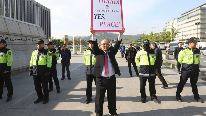 A South Korean protester holds up a placard opposing a plan to deploy the advanced U.S. missile defense system called Terminal High-Altitude Area Defense, or THAAD, near U.S. Embassy in Seoul, South Korea, Thursday, April 27, 2017.