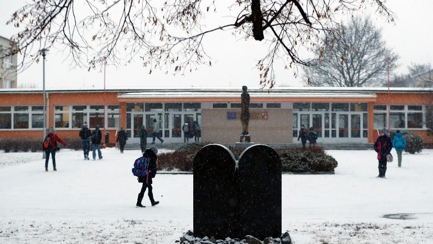 In this picture taken on Tuesday, Jan. 31, 2017, children walk to school past a memorial to a former Jewish cemetery in Prostejov, Czech Republic. A Jewish foundation said Friday, April 28, 2017 it discovered this week that the tombstone of Prostejov Rabbi Zvi Horowitz, who died in 1816 was broken into two pieces. (AP Photo/Petr David Josek)