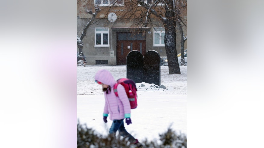 In this picture taken on Tuesday, Jan. 31, 2017, a young girl walks to school past a memorial to a former Jewish cemetery in Prostejov, Czech Republic. A Jewish foundation said Friday, April 28, 2017 it discovered this week that the tombstone of Prostejov Rabbi Zvi Horowitz, who died in 1816 was broken into two pieces. (AP Photo/Petr David Josek)