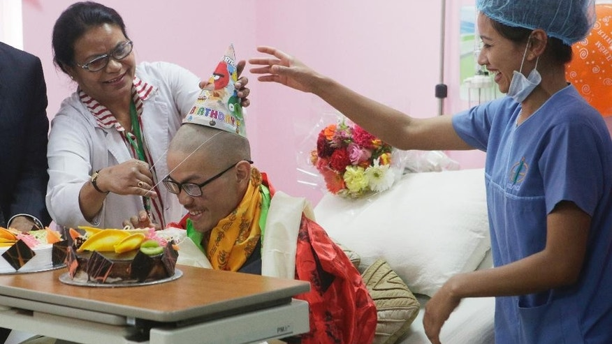 Medical staff congratulate Taiwanese trekker Liang Sheng-yueh during a birthday celebration at Grandee International Hospital in Kathmandu, Nepal, Friday, April 28, 2017. The Taiwanese man who was rescued on Wednesday after 47 days on a mountain in Nepal has celebrated his 21st birthday at a hospital in the capital. (AP Photo/Niranjan Shrestha)