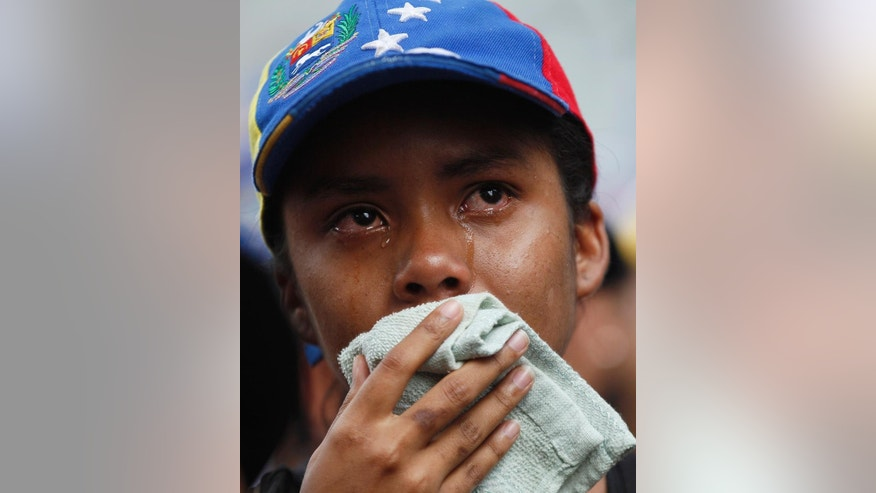 A woman cries during an homage to Juan Pablo Pernalete in Caracas, Venezuela, Thursday, April 27, 2017. Pernalete, the latest victim of Venezuela's unrest, was killed during anti-government protests Wednesday when he was struck by a tear gas canister fired by security forces. (AP Photo/Ariana Cubillos)