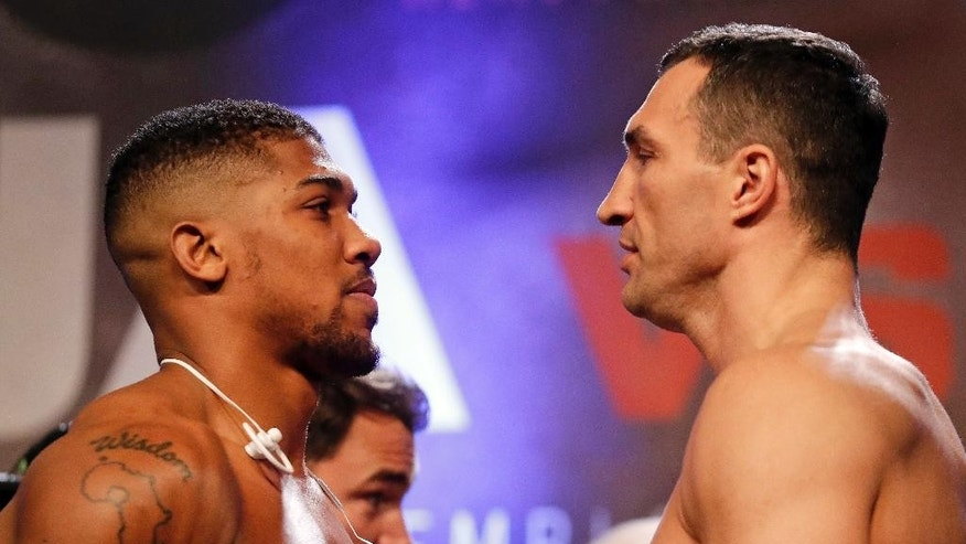 British boxer Anthony Joshua, left, and Ukrainian boxer Wladimir Klitschko take part in their weigh-in at Wembley Arena in London, Friday, April 28, 2017. They are due to fight for Joshua's IBF and the vacant WBA Super World/IBO heavyweight titles on Saturday at Wembley stadium in London. (AP Photo/Matt Dunham)