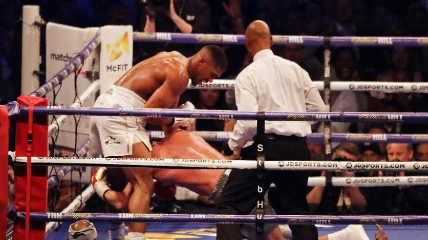British boxer Anthony Joshua, left, knocks down Ukrainian boxer Wladimir Klitschko during their fight for Joshua's IBF and the vacant WBA Super World and IBO heavyweight titles at Wembley stadium in London, Saturday, April 29, 2017. (AP Photo/Matt Dunham)