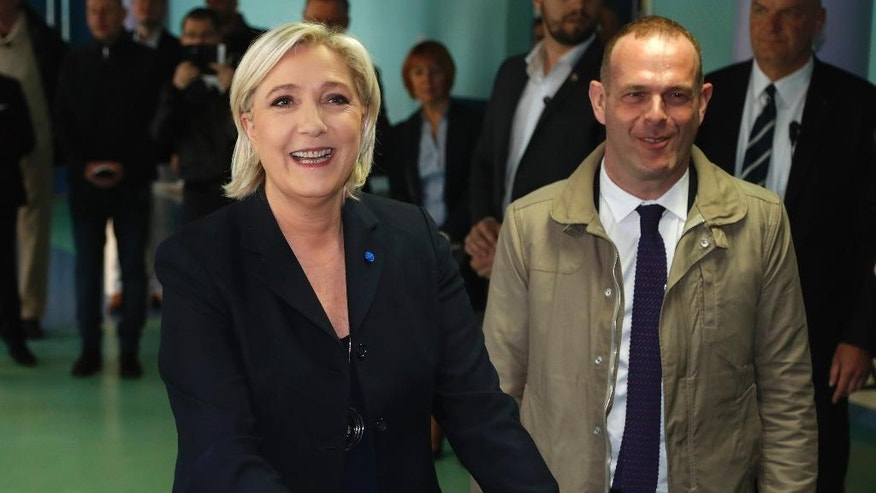 FILE - In this April 23, 2017 file photo, far-right leader and candidate for the 2017 French presidential election Marine Le Pen casts her vote for the first-round presidential election while National Front Henin-Beaumont's mayor Steeve Briois, right, looks on, in Henin-Beaumont, northern France. Briois replaces Jean-Francois Jalkh as interim National Front leader after Le Pen said she would step aside to concentrate on her campaign. (AP Photo/Frank Augstein, File)