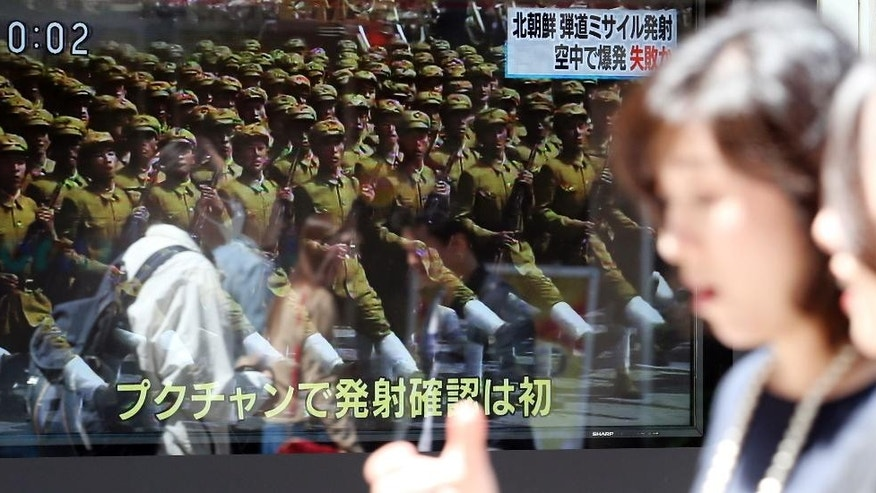 People walk past a TV news showing an image of North Korean troops while reporting North Korea's missile test, in Tokyo, Saturday, April 29, 2017. A North Korean mid-range ballistic missile apparently failed shortly after launch Saturday, South Korea and the United States said, the third test-fire flop just this month but a clear message of defiance as a U.S. supercarrier conducts drills in nearby waters. (AP Photo/Koji Sasahara)