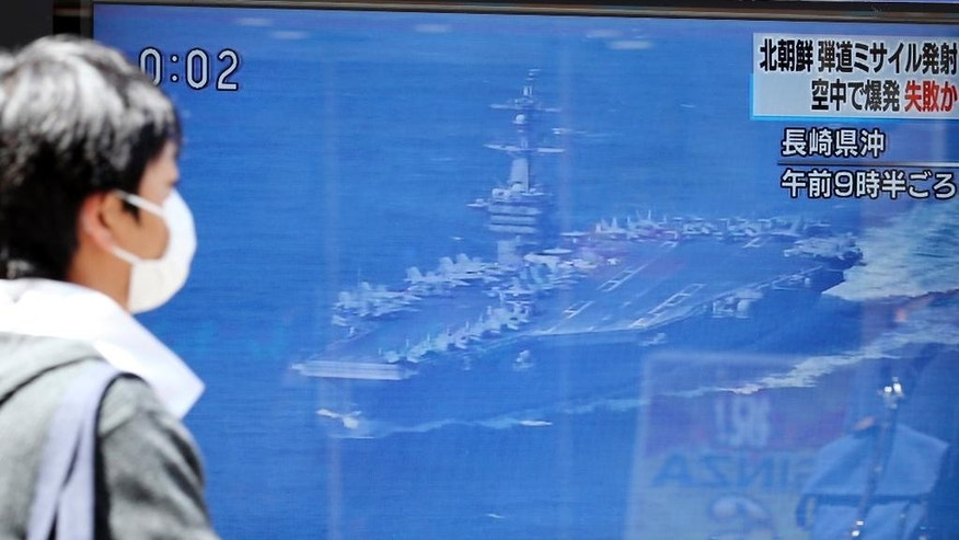 A man walks past a TV news showing an image of USS aircraft carrier Carl Vinson while reporting North Korea's missile test, in Tokyo, Saturday, April 29, 2017. A North Korean mid-range ballistic missile apparently failed shortly after launch Saturday, South Korea and the United States said, the third test-fire flop just this month but a clear message of defiance as a U.S. supercarrier conducts drills in nearby waters. (AP Photo/Koji Sasahara)
