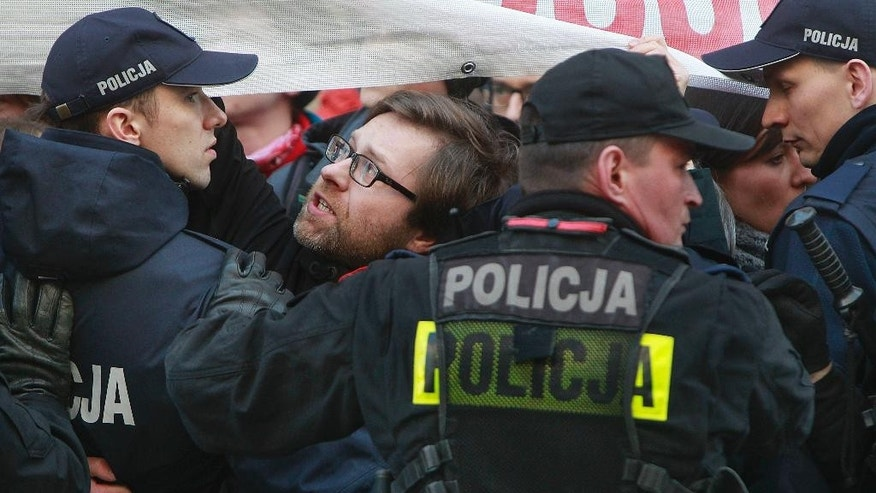 Polish police use force to remove anti-nationalist protesters who are trying to block the march of a nationalist organization the National-Radical Camp whose members we marching through downtown Warsaw, Poland on Saturday, April 29,  2017, to mark 83 years of their organization. The protesters were not given permission to hold their action, prompting police action. (AP Photo/Czarek Sokolowski)