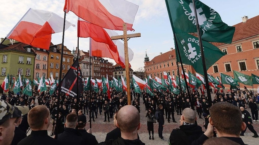 Members of nationalist organization the National-Radical Camp display national and organization flags and chant anti-migrant slogans during a march to mark 83 years of their organization, in Warsaw, Poland, Saturday, April 29, 2017. (AP Photo/Czarek Sokolowski)