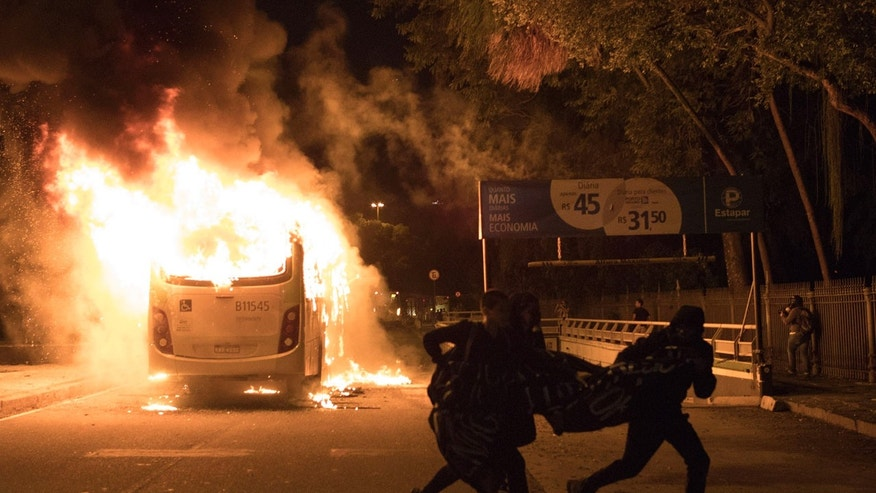 Demonstrators run past a bus set fire by protesters during a general strike protest in Rio de Janeiro, Brazil, Friday, April, 28, 2017