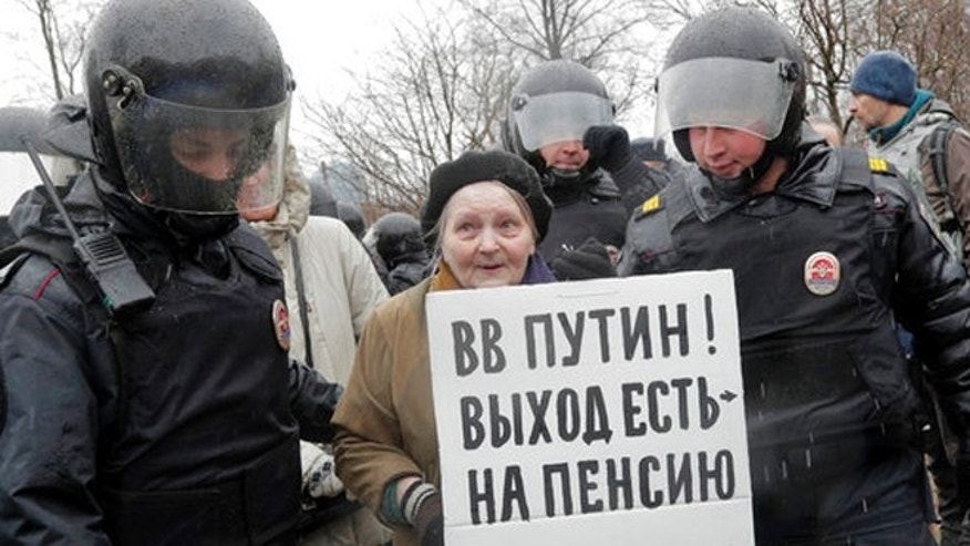 Policemen detain a participant in an unauthorized rally in St. Petersburg, Russia, Saturday.