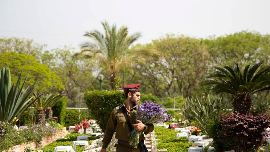 An Israeli soldiers holds flowers to be placed on a graves of fallen soldiers on the eve of memorial Day in Kiryat Shaul military cemetery in Tel Aviv, Israel, Sunday, April 30, 2017. Israel marks the annual Memorial Day in remembrance of soldiers who died in the nation's conflicts, beginning at dusk Sunday until Monday evening. (AP Photo/Ariel Schalit)