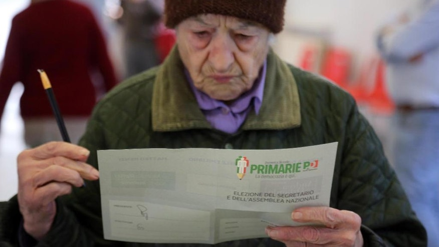 A woman checks her ballot as she prepares to vote for Democratic party's primary elections, in Bologna, Italy, Sunday, April 30, 2017.  The three candidates are former Italian Premier Matteo Renzi, Governor of Apulia region, Michele Emiliano, and Justice Minister Andrea Orlando. (Giorgio Benvenuti/ANSA via AP)