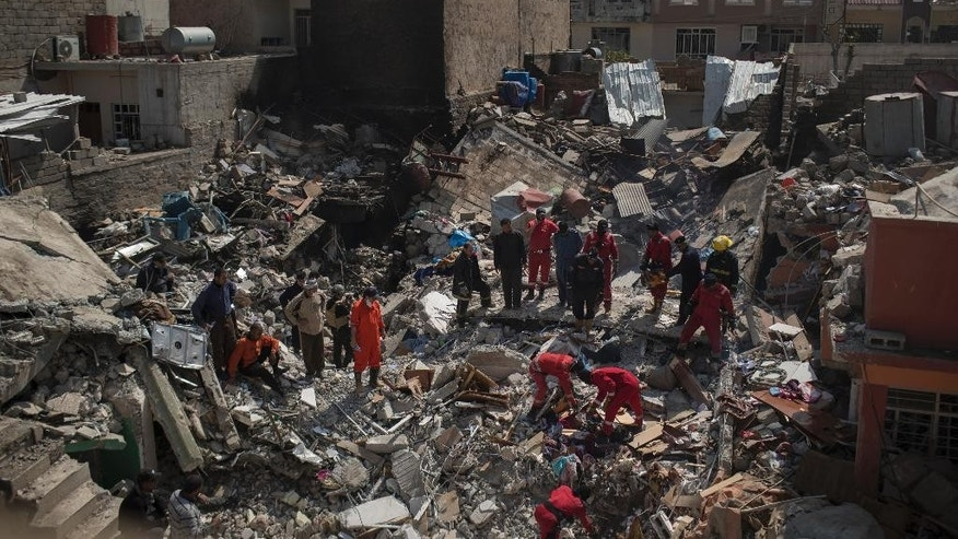 "FILE - In this March 24, 2017 file photo, civil protection rescue teams work on the debris of a destroyed house to recover the body of people killed in an airstrike during fighting between Iraqi security forces and Islamic State militants on the western side of Mosul, Iraq.  In a statement released Sunday, April 30, 2017, the Pentagon said investigations conducted during the month of March reveal that coalition airstrikes killed 45 civilians, mostly in and around the city of Mosul. The Pentagon said in each incident ""all feasible precautions were taken,"" but the strikes still resulted in ""unintentional"" loss of civilian life. (AP Photo/Felipe Dana, File)"
