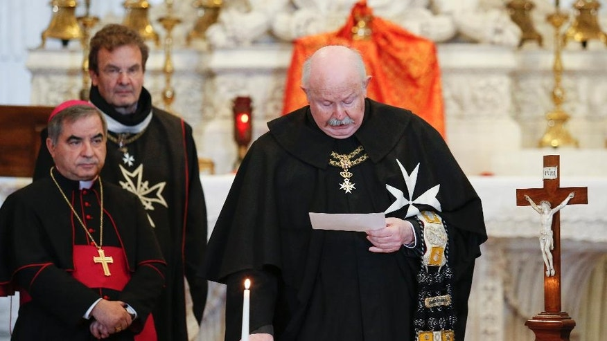 Fra' Giacomo Dalla Torre, the Knights of Malta newly Lieutenant of the Grand Master, takes his oath next to Archbishop Angelo Becciu, left,  at the order's Villa Magistrale on Rome's Aventine Hill, Sunday, April 30, 2017.  The ancient Knights of Malta religious order voted for a new leader after the old one was effectively ousted by Pope Francis. (Remo Camilli via AP)