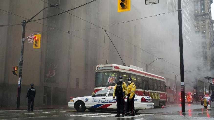 Police block the street as smoke pours into the air following a series of loud blasts were heard in Toronto on Monday, May 1, 2017. (Graeme Roy/The Canadian Press via AP)