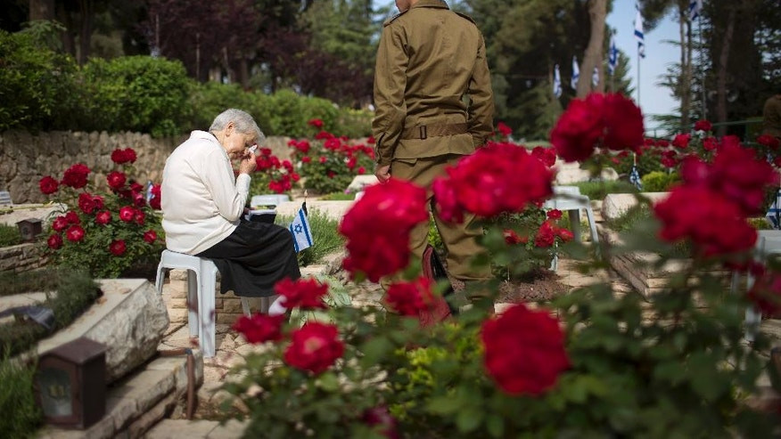 Esther Moses mourn over her cousin Menahem Frider's grave, during Memorial Day ceremony at Mt. Herzl military cemetery in Jerusalem, Monday, May 1, 2017. Israelis came to a two-minute standstill to remember fallen soldiers and victims of terror as the country marked Memorial Day, one of the most somber days on its calendar. (AP Photo/Oded Balilty)