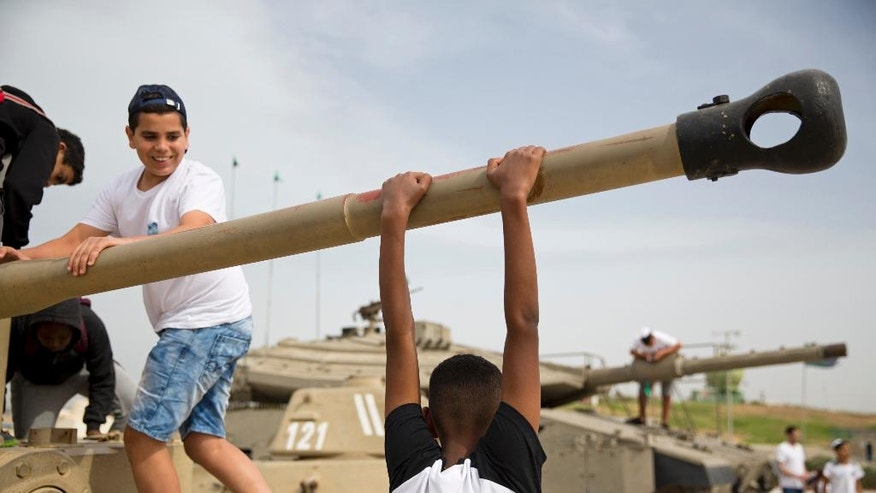 Children climb on an old tank at the Armored Corps memorial site before a ceremony marking the annual Memorial Day to remember fallen soldiers and victims of terror, one of the most somber days on its calendar, in Latrun, Israel, Monday, May 1, 2017. (AP Photo/Ariel Schalit)