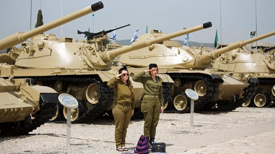Two Israeli soldiers salute as they observe two minutes of silence as an air raid sirens sounds, in Latrun, Israel, Monday, May 1, 2017. Israelis came to a two-minute standstill to remember fallen soldiers and victims of terror as the country marked Memorial Day, one of the most somber days on its calendar. (AP Photo/Ariel Schalit)