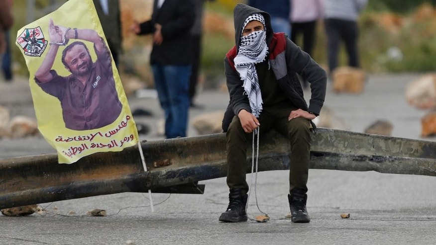 "FILE -- In this April 23, 2017 file photo, a Palestinian protester holds a sling shot as he sits near a banner with a picture of jailed leader Marwan Barghouti that reads, ""The architect of the uprising,"" following a protest supporting prisoners in Israeli jails, in the West Bank city of Ramallah. An Israeli official said Monday, May 1, 2017, that the number of Palestinians prisoners participating in one of the largest hunger strike in years dropped to 870, from 1,300 a week earlier. Support for the hunger strikers who seek better conditions has gained momentum with West Bank marches and a social media campaign and has boosted the Palestinian leadership credentials of its imprisoned organizer, Barghouti. (AP Photo/Majdi Mohammed, File)"