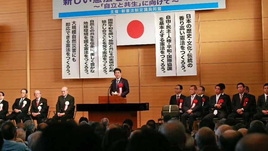 Japanese Prime Minister Shinzo Abe, center, makes a speech during the annual rally on revising Japan's constitution organized by ruling party lawmakers in Tokyo, Monday, May 1, 2017. Abe has pledged to initiate debate in parliament on revising the country's U.S.-drafted constitution. The democratic and pacifist charter took effect 70 years ago on May 3. (AP Photo/Shizuo Kambayashi)
