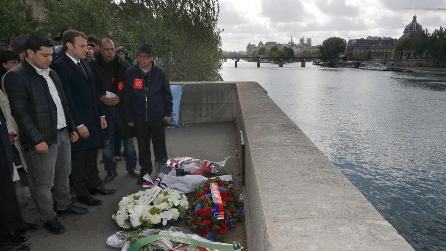 French centrist presidential candidate Emmanuel Macron, 2nd left, stands next to Said Bouarram, left, son of Brahim Bouarram, as he pays hommage to Brahim Bouarram, a Moroccan who drowned in 1995 when right-wing extremists threw him from a bridge after a National Front rally, during a ceremony on the banks of the Seine River in Paris, France, Monday, May 1, 2017. (Philippe Wojazer/Pool Photo via AP)