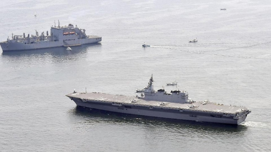 Japan's helicopter carrier JS Izumo, foreground, sails by a U.S. supply ship, top left, at anchor in the waters off Yokosuka after the Japanese destroyer departed Yokosuka port, south of Tokyo, Monday, May 1, 2017.  Japan's navy has dispatched its largest destroyer reportedly tasked with escorting U.S. military ships off the Japanese coast, a first-time mission under new security legislation that allows Japan's military a greater role overseas, amid heightened tension on the Korean Peninsula. The Izumo started to escort the U.S. supply ship after the two vessels met up in the waters off the Boso Peninsula, south of Tokyo, later in the day. (Ren Onuma/Kyodo News via AP)