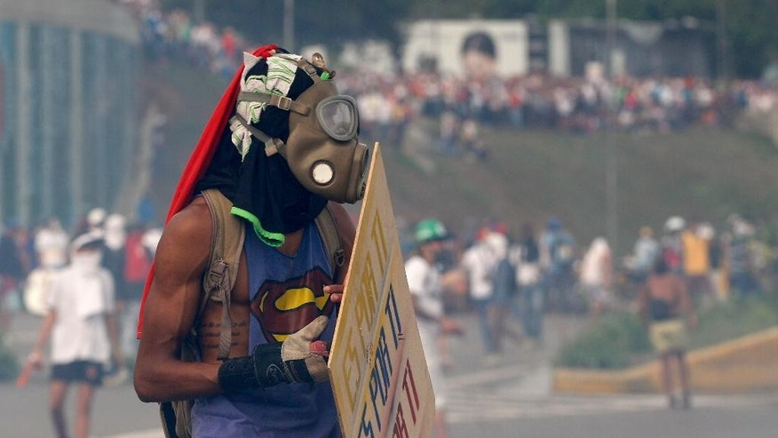 A demonstrator wears a mask during an opposition May Day march in Caracas, Venezuela, Monday, May 1, 2017. Venezuelans are taking to the streets in dueling anti- and pro-government May Day demonstrations as an intensifying protest movement enters its second month. (AP Photo/Ariana Cubillos)