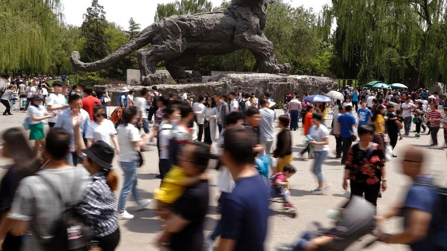 Visitors, some with their children, walk past a giant tiger sculpture on display at a zoo on the May Day holiday in Beijing, Monday, May 1, 2017. Millions of Chinese are taking advantage of the May Day holidays to visit popular tourist sites. (AP Photo/Andy Wong)