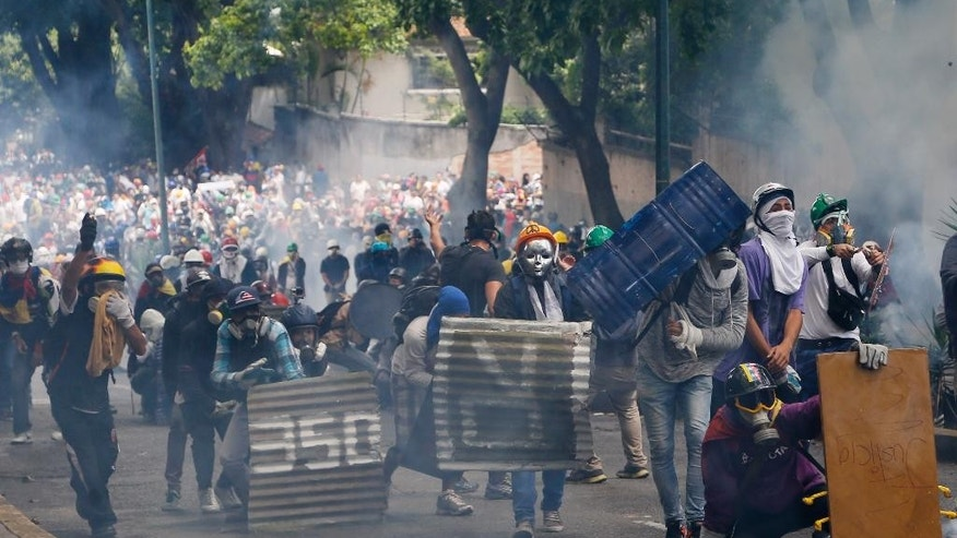 Masked and helmeted demonstrators face off with security forces during an opposition May Day march in Caracas, Venezuela, Monday, May 1, 2017. Venezuelans are taking to the streets in dueling anti- and pro-government May Day demonstrations as an intensifying protest movement enters its second month. (AP Photo/Ariana Cubillos)