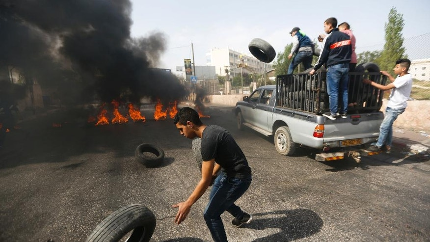 FILE -- In this Thursday, April 27, 2017 file photo, Palestinian protesters burn tires during a general strike in support of Palestinian prisoners on hunger strike in Israeli jails, in the West Bank city of Ramallah. Palestinian President Mahmoud Abbas' initial relief over having been invited to the White House is now clouded by concerns that he will have to say no to President Donald Trump in their first meeting Wednesday, May 3, 2017.  (AP Photo/Majdi Mohammed, File)
