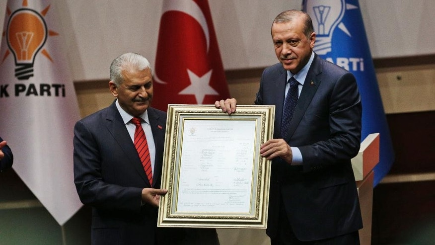 Turkey's President Recep Tayyip Erdogan, right, poses for photograph with Turkey's Prime Minister Binali Yildirim, left, during a ceremony to rejoin the ruling Justice and Development Party, or AKP, in Ankara, Turkey, Tuesday, May 2, 2017. Erdogan is to rejoin the Islamic-rooted party he co-founded in a ceremony on Tuesday, following his narrow victory in a referendum that expands the powers of the president's office. (AP Photo/Burhan Ozbilici)
