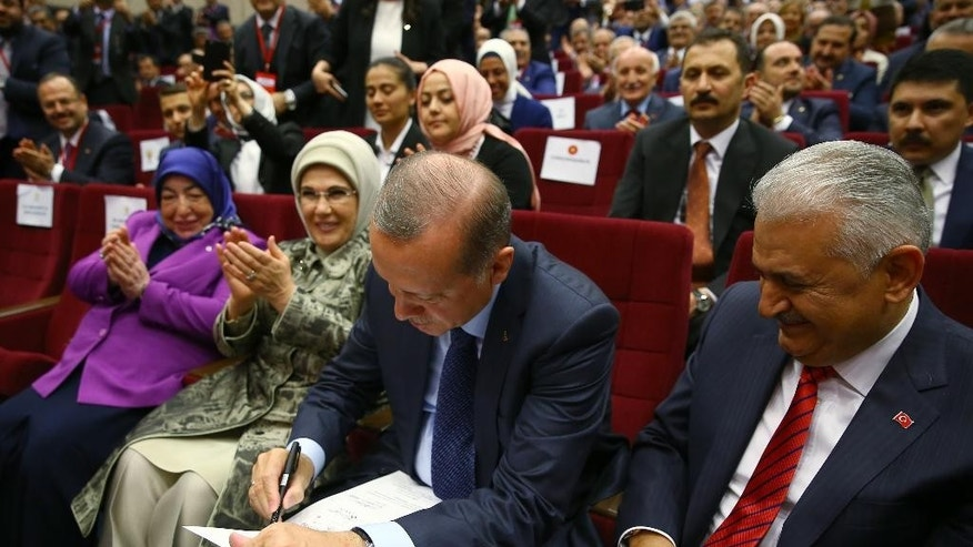 Turkey's President Recep Tayyip Erdogan, enter signs a declaration of membership to rejoin the ruling Justice and Development Party, or AKP, in Ankara, Turkey, as Turkey's Prime Minister Binali Yildirim, right, looks on during a ceremony, Tuesday, May 2, 2017. Erdogan rejoined the Islamic-rooted party he co-founded in a ceremony on Tuesday, following his narrow victory in a referendum that expands the powers of the president's office. (Press Presidency Press Service via AP, Pool)
