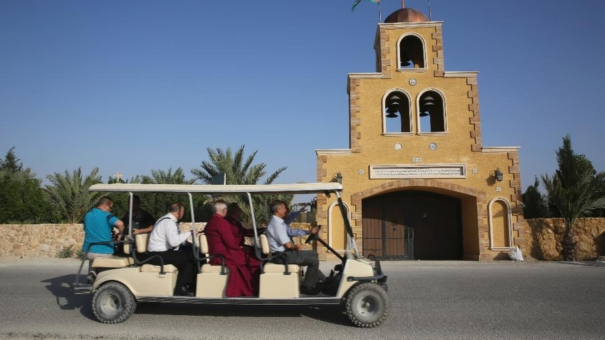 "The Archbishop of Canterbury, Justin Welby, center, takes a golf cart past a church at the baptism site al-Maghtas in Jordan Wednesday. May, 3, 2017.  The head of the Anglican church was on a visit to the region to meet refugees including Christians from Iraq and King Abdullah II.  He pledged support for the refugees in Europe as well as in the Middle East. ""We do not want a Middle East without Christians. Christians are the past in the Middle East, they are the present and they must be the future,"" said the archbishop. (AP Photo/Sam McNeil)"