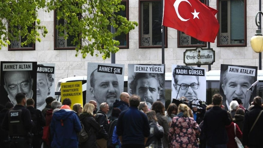 Marking the World Press Freedom Day, activists with Reporters Without Borders hold posters with portraits of journalists detained in Turkey, to protest against the situation for media in the country, in front of the Turkish embassy in Berlin, Wednesday, May 3, 2017. The German language poster reads: 'Freedom for detained Journalists'. (AP Photo/Markus Schreiber)