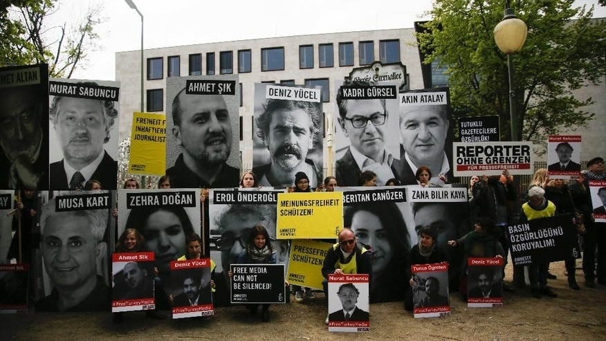 Marking the World Press Freedom Day, activists with Reporters Without Borders hold posters with portraits of journalists detained in Turkey, to protest against the situation for media in the country, in front of the Turkish embassy in Berlin, Wednesday, May 3, 2017. The German language poster from left reads: 'Freedom for detained Journalists', 'Save freedom of opinion' and 'Save press freedom'. (AP Photo/Markus Schreiber)
