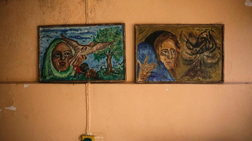 In this Sunday, April 30, 2017 photo, works by the Iraqi painter Mustafa al-Taee hang on the wall of his home in the northern town of Hamam al-Alil, near Mosul, Iraq. After the Islamic State group swept into his town nearly three years ago, al-Taee resolved to bear witness to the militants' brutal rule by secretly painting what he had seen with his own eyes. The result was a gallery of horrors. (AP Photo/ Bram Janssen)