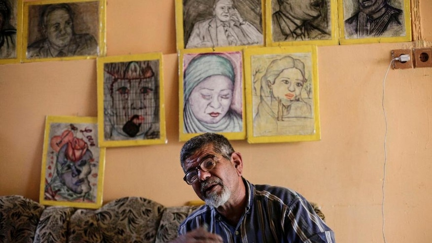 In this Sunday, April 30, 2017 photo, Iraqi painter Mustafa al-Taee sits in front of a display of his art work as he speaks to The Associated Press, at his home in the northern town of Hamam al-Alil, near Mosul, Iraq. After the Islamic State group swept into his town nearly three years ago, al-Taee resolved to bear witness to the militants' brutal rule by secretly painting what he had seen with his own eyes. The result was a gallery of horrors: car bombs, dead children, an IS defector beheaded in a public square, a former police officer strung up by his legs for hours before being shot dead. (AP Photo/ Bram Janssen)
