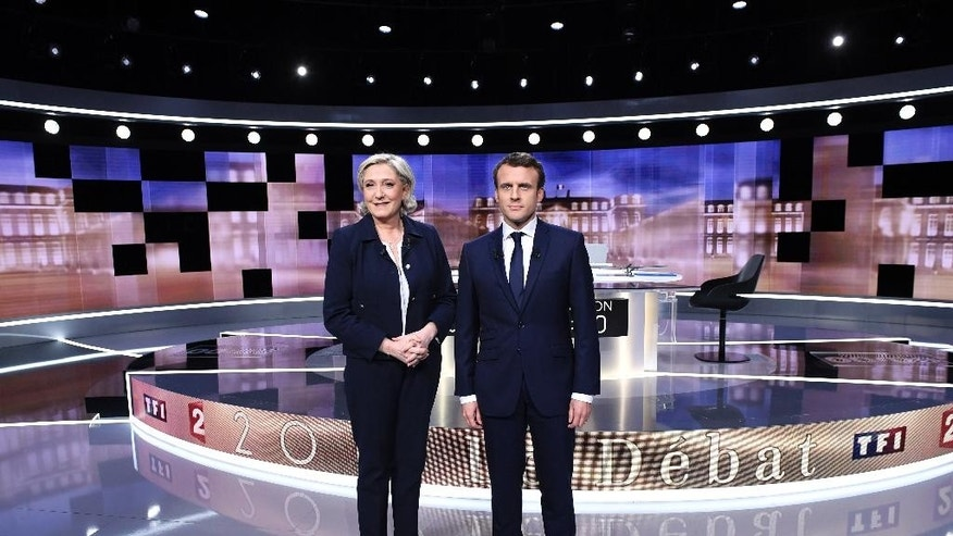 French presidential election candidate for the far-right Front National party, Marine Le Pen, left, and French presidential election candidate for the En Marche ! movement, Emmanuel Macron, pose prior to the start of a live broadcast face-to-face televised debate in La Plaine-Saint-Denis, north of Paris, France, Wednesday, May 3, 2017 as part of the second round election campaign. Pro-European progressive Emmanuel Macron and far-right Marine Le Pen are facing off in their only direct debate before Sunday's presidential runoff election. (Eric Feferberg/Pool Photo via AP)