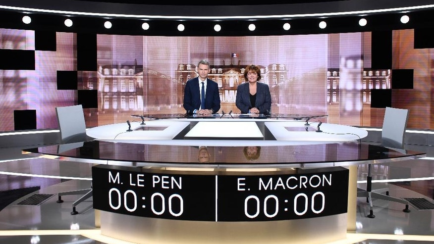Journalists Christophe Jakubyszyn, left, and Nathalie Saint-Cricq pose Tuesday May 2, 2017 in La Plaine Saint Denis, outside Paris, shows the TV studio where French presidential candidates will debate Wednesday, four days before the vote for the second round. Centrist presidential candidate Emmanuel Macron will debate with far-right candidate Marine Le Pen. (Eric Feferberg, Pool via AP)