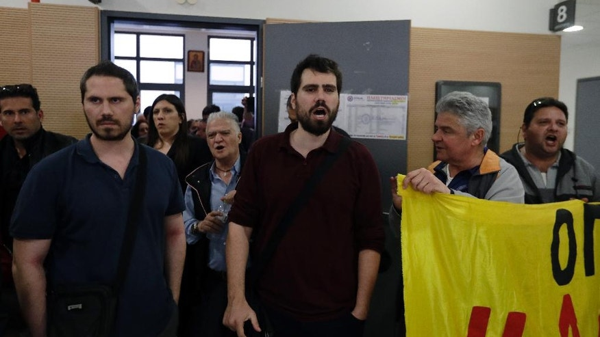 In this Wednesday, March 22, 2017 photo Leonidas Papadopoulos, left, stands outside a court room as his brother Ilias, center, shout slogans with other protesters in Athens. The bearded brothers have created a nationwide protest network of several hundred volunteers to disrupt the auctions across Greece and to help illegally reconnect homes of unemployed people who have had their electricity cut off. In its fourth year, the campaign is intensifying as the country faces pressure from its international bailout creditors to deal with a mountain of bad bank loans. (AP Photo/Thanassis Stavrakis)