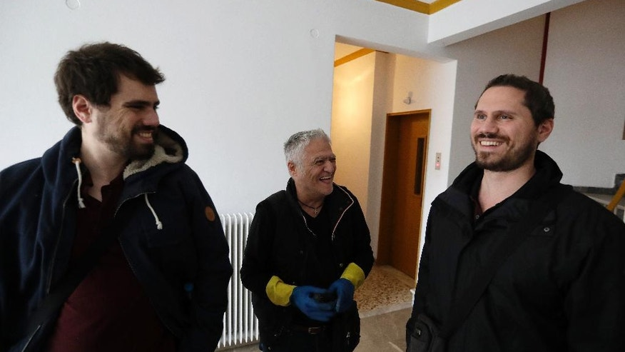 In this Wednesday, April 5, 2017 photo Leonidas Papadopoulos, left, and his brother Ilias, right, with Dimitris a volunteer electrician laugh as they have reconnected the power to the grid at an unemployed resident's home in Athens. The bearded brothers have created a nationwide protest network of several hundred volunteers to disrupt the auctions across Greece and to help illegally reconnect homes of unemployed people who have had their electricity cut off. In its fourth year, the campaign is intensifying as the country faces pressure from its international bailout creditors to deal with a mountain of bad bank loans. (AP Photo/Thanassis Stavrakis)