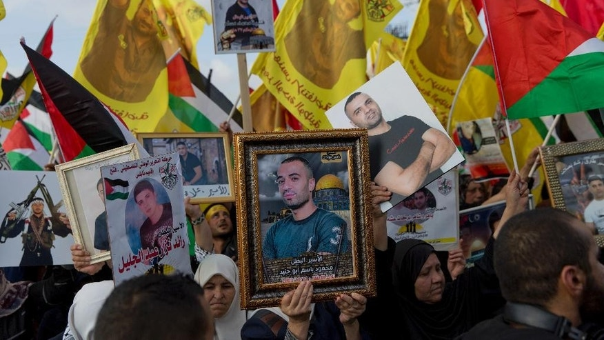 "Protesters carry pictures of jailed Palestinian prisoners during a rally supporting prisoners in Israeli jails, who have been on an open-ended hunger strike for the past 17 days, in the West Bank city of Ramallah, Wednesday, May 3, 2017. The prisoners launched the protest to press for better conditions, including family visits. The International Committee of the Red Cross issued a rare statement, urging Israeli authorities to stop what it called the ""systematic suspension"" of family visits for the hunger strikers. (AP Photo/Nasser Nasser)"