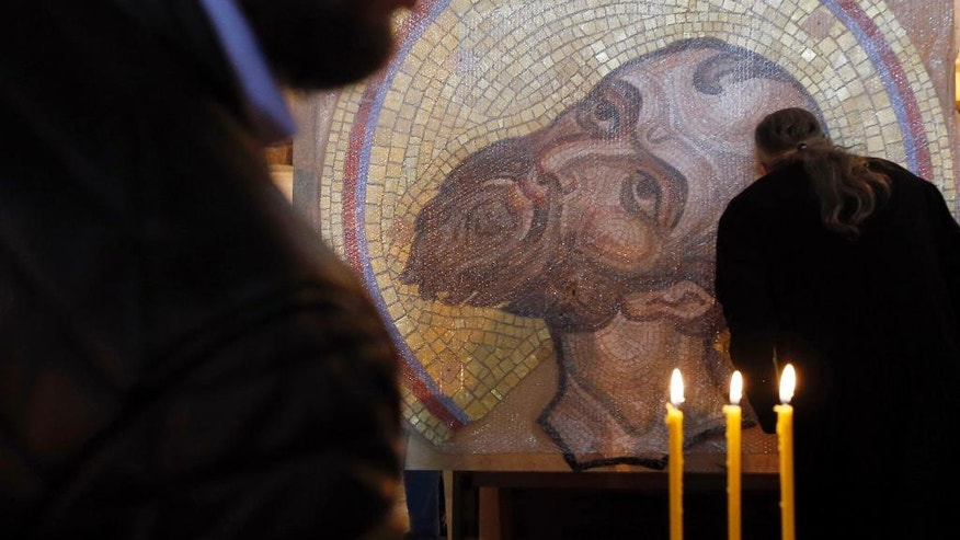 A priest kisses a mosaic from Russia depicting Jesus Christ that will decorate the inside of St. Sava Temple in Belgrade, Serbia, Wednesday, May 3, 2017. Russia has been looking to increase its sway in fellow-Orthodox Christian Serbia, a Moscow ally in the Balkans. (AP Photo/Darko Vojinovic)
