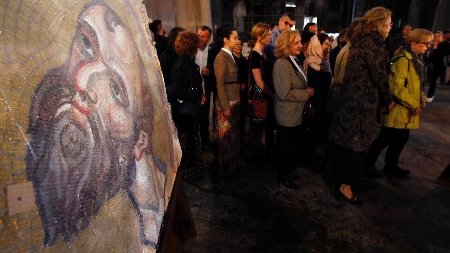 People attend a service next to a mosaic from Russia depicting Jesus Christ that will decorate the inside of St. Sava Temple in Belgrade, Serbia, Wednesday, May 3, 2017. Russia has been looking to increase its sway in fellow-Orthodox Christian Serbia, a Moscow ally in the Balkans. (AP Photo/Darko Vojinovic)