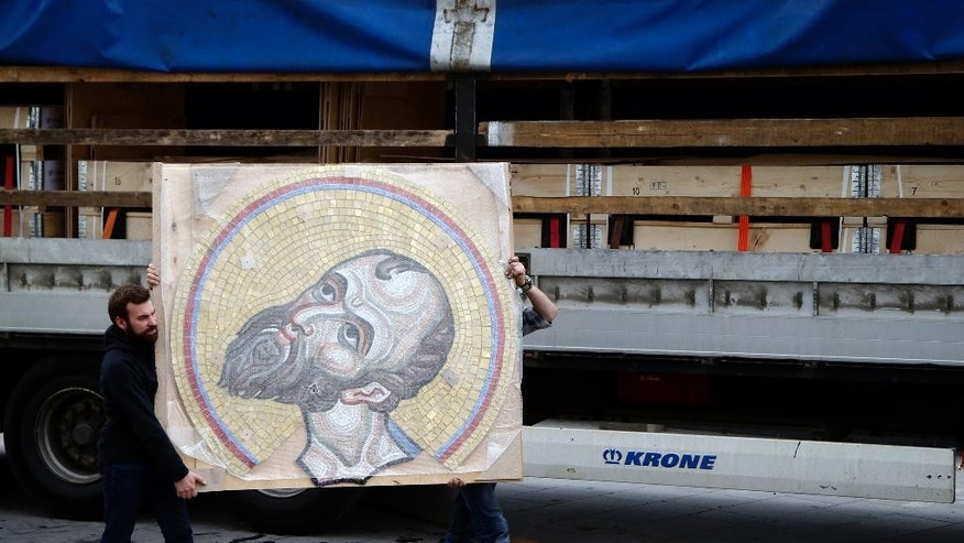 Workers carry a mosaic from Russia depicting Jesus Christ that will decorate the inside of St. Sava Temple in Belgrade, Serbia, Wednesday, May 3, 2017. Russia has been looking to increase its sway in fellow-Orthodox Christian Serbia, a Moscow ally in the Balkans. (AP Photo/Darko Vojinovic)