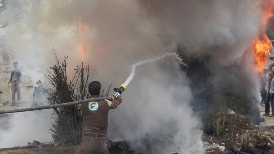 This photo provided by Azaz Media Office, a Syrian anti-government activist group, which has been authenticated based on its contents and other AP reporting, shows a Syrian White Helmet civil defense worker extinguishing a burning car at the explosion scene, in Azaz town, north Syria, Wednesday, May 3, 2017. Syrian activists say a large explosion in a northern town along the border with Turkey has killed and wounded several people. (Azaz Media Office via AP)