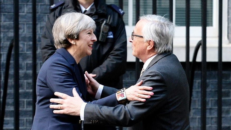 "FILE - In this April 4, 2017 file photo, Britain's Prime Minister Theresa May greets European Commission President Jean-Claude Juncker outside 10 Downing Street in London. Theresa May acknowledged Tuesday May 2, 2017 that Brexit ""will not be easy,"" after EU officials accused Britain of underestimating the complexity of the task ahead. (John Stillwell/PA via AP)"